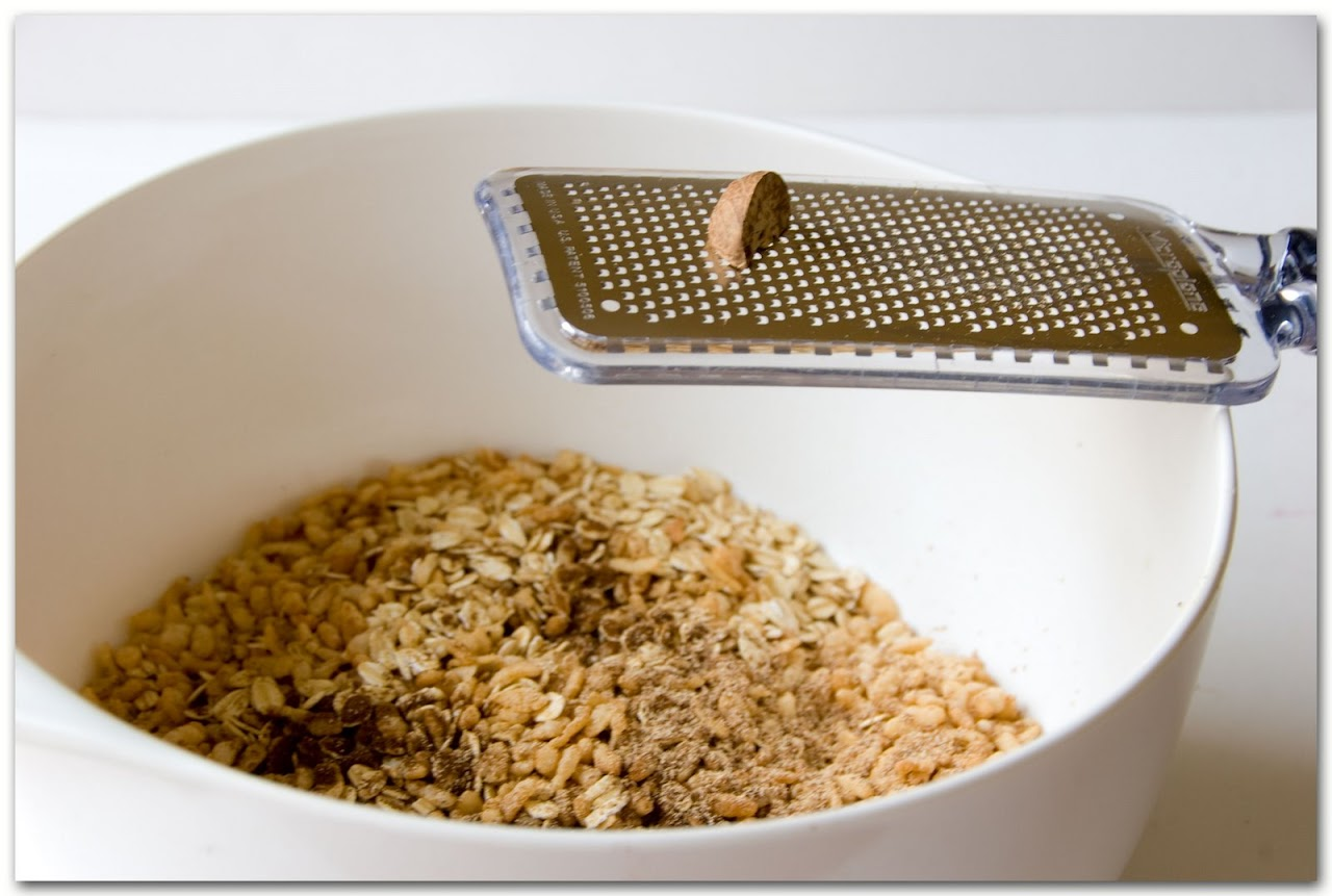 Grating nutmeg into dry granola mixture