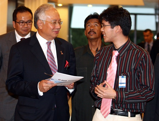 Prime Minister of Malaysia receiving the report from One Young World Delegate, Michael Teoh, in 2010