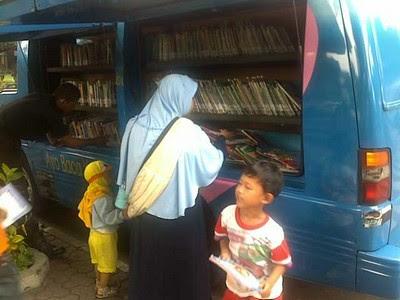 Seorang ibu dan dua orang anaknya memilih buku di perpustakaan keliling.