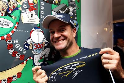 Рубенс Баррикелло на фоне плаката Jim Bamber