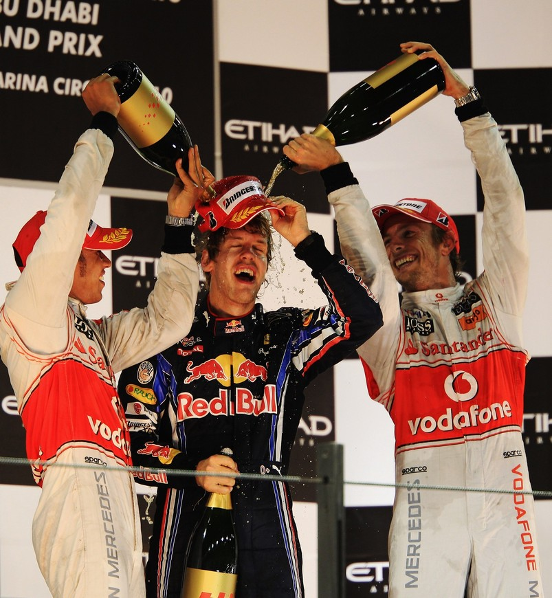 Льюис Хэмилтон и Дженсон Баттон поливают Себастьяна Феттеля победным шампанским на Гран-при Абу-Даби 2010