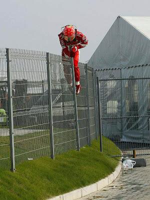 Михаэль Шумахер перелезает через забор после вылета на Гран-при Китая 2005