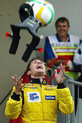 Джанкарло Физикелла подбрасывает шлем на Гран-при Бразилии 2003