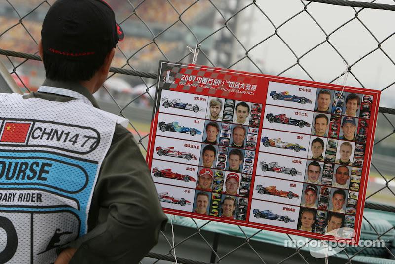 маршал на Гран-при Китая 2007 изучает фотографии гонщиков