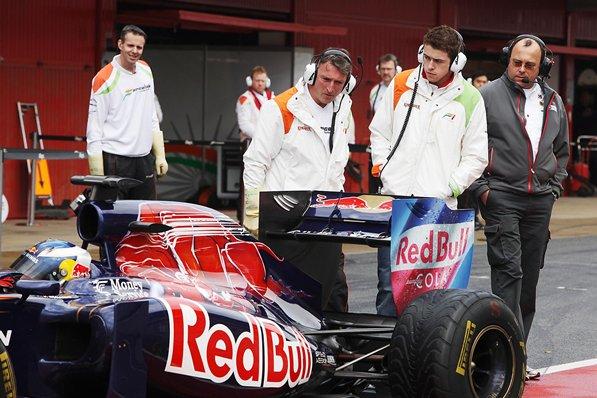 механики Force India и Пол ди Реста наблюдают за задней частью болида Toro Rosso Даниэля Риккардо на предсезонных тестах 2011 в Барселоне