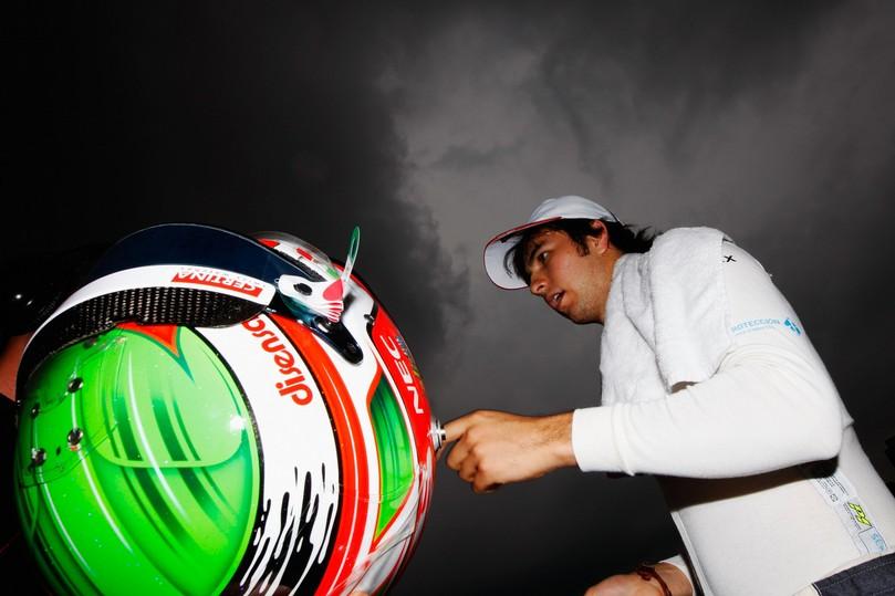 Серхио Перес идет со шлемом на фоне темного неба на Гран-при Малайзии 2011