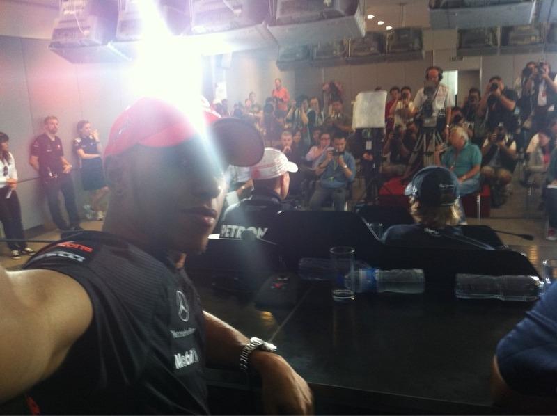 Льюис Хэмилтон снимает самого себя на камеру мобильного телефона на фоне пресс-конференции на Гран-при Китая 2011