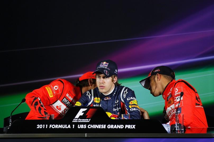 Дженсон Баттон и Льюис Хэмилтон разговаривают за спиной Себастьяна Феттеля на пресс-конференции после квалификации на Гран-при Китая 2011