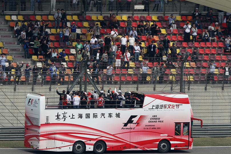 автобус с гонщиками проезжает мимо болельщиков на Гран-при Китая 2011