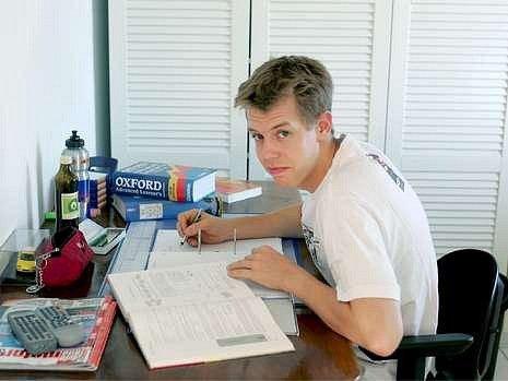 молодой Себастьян Феттель с учебником и тетрадкой за уроками