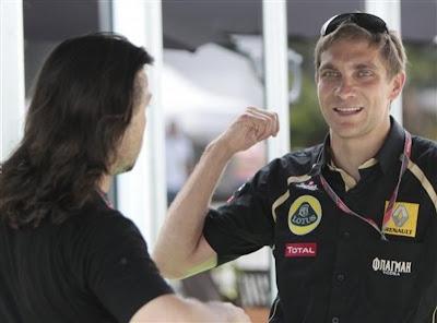 жестикулирующий Виталий Петров разговаривает с кем-то на Гран-при Малайзии 2011