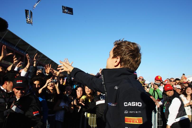 Себастьян Феттель бросает карточки с автографом болельщикам Истамбула на Гран-при Турции 2011