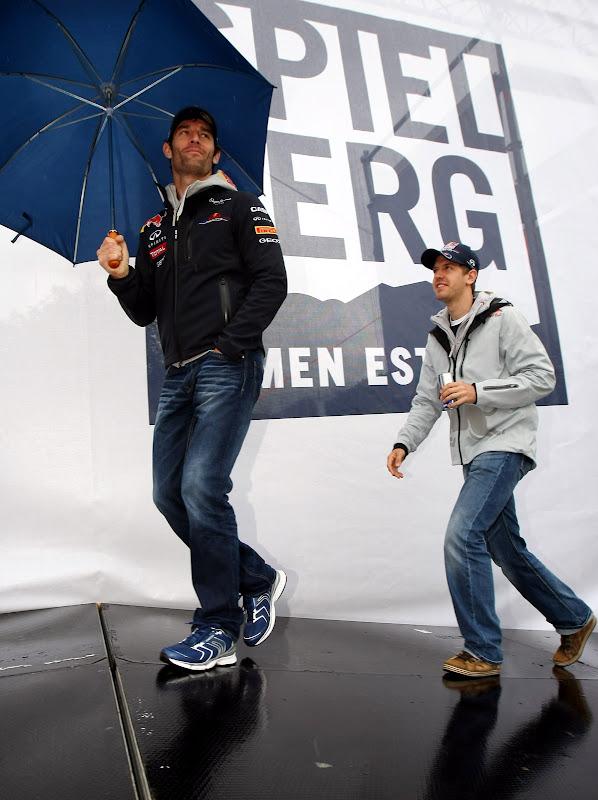 Себастьян Феттель следует за Марком Уэббером с зонтиком на открытии трассы Red Bull Ring 15 мая 2011