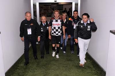 Себастьян Феттель идет по коридору в футбольной форме