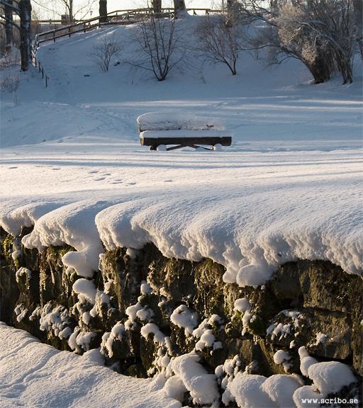 Vinterbild på en bänk på gäsmattan bakom Ulva kvarn