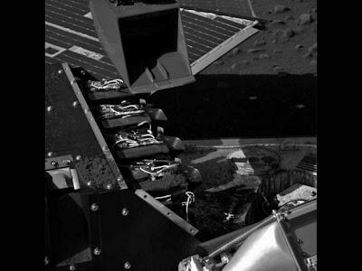 Phoenix'in yüzey görüntüleme aracından alınan fotoğrafta, robotik koldaki kepçenin laboratuvar üzerinde konumlandığı görülüyor.