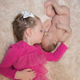 Siblings by Carole Brown - Babies & Children Child Portraits ( laying down, kissing brother, pink shirt, 9 day old boy, 2 year old gir )