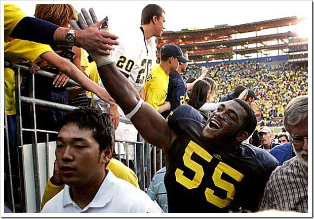 (caption) Michigan defensive end Brandon Graham high fives fans as he heads to the locker room after the Wolverines' victory.  *** Michigan rallies back from a 19-0 deficit to stun the ninth-ranked Wisconsin Badgers 27-25, giving new head coach Rich Rodriguez a victory in his first Big Ten game. *** The Michigan Wolverines (1-2) host the 9th-ranked Wisconsin Badgers in U-M head coach Rich Rodriguez' first Big Ten game. Photos taken on Saturday, September 27, 2008.  ( John T. Greilick / The Detroit News )