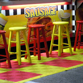 Take a seat, have a bite by Kaye Petersen - City,  Street & Park  Amusement Parks ( sausage, red, food, night, yellow, stools )