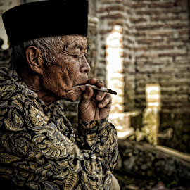 Enjoying a cigarette by Santoso Wibowo - People Portraits of Men
