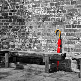 The Red Umbrella by Kaye Menner - Buildings & Architecture Other Exteriors ( old wall, old, peeling paint, textured bricks, brick wall, bench, old bricks, kaye menner photography, kaye menner, brick background, painted bricks, bench seat, bricks, red umbrella, peeling, texture, old paint, umbrella, chunky bench, paint, textured wall, white paint, painted wall, timber bench, wall, selective color, pwc )