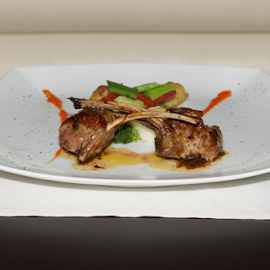 Lamb cutlets with vegetables and place setting by Nick Dale - Food & Drink Meats & Cheeses ( haute cuisine, peppers, fork, main course, green, potatoes, white, vegetables, plate, cutlery, lamb, restaurant, dinner, cutlets, red, food, broccoli, entree, gourmet, knife, china )