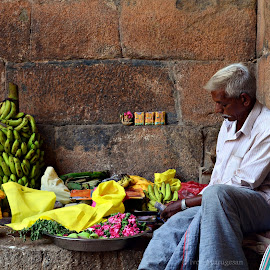 flower seller in a temple complex by Ivon Murugesan - People Street & Candids ( wood, black and white, street, statues, rock, architecture, yellow, people, photography, city, sculptures, blackandwhite, oldman, india, flowers, black, flower, abstract, work, potrait, green, carving, white, candid, street photography, temple, statue, peoples, streets, scultpure, potraits )