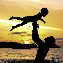 Flying High by Troy Wheatley - People Family ( water, child, orange, mommy, silhouette, sunset, baby, toss,  )
