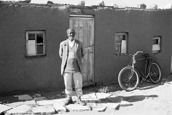Mr Cwaile, Valspan activist, outside his home. Valspan was an area threatened by apartheid forced removals. The residents were not allowed to repair their homes and only very basic services were provided. The apartheid government then designated the area a 'slum'. The number on the door indicates that removal is immanent.