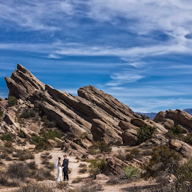 True love stands by each others side on good days and stands even closer on bad days by Yansen Setiawan - Wedding Bride & Groom ( desserts, blue sky, wedding, bride and groom, landscape, rocks )