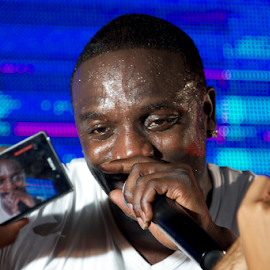 Close-up of black singer Akon with iPhone by Nick Dale - People Musicians & Entertainers ( concert, t-shirt, white, singer, turkey, iphone, bodrum, stage, black, akon )