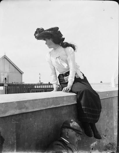 Woman sitting on a wall, possibly at one of the Kingstown line stations