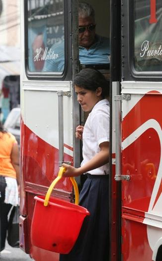 Una  joven estudiante baja de un autobús del transporte colectivo, luego de ofrecer refrescos a las pasajeros, como parte del trabajo que realiza después de su jornada escolar. El trabajo infantil es una de las peores formas de explotación y abuso ya que pone en peligro la salud, seguridad y educación de los más chicos. Foto de La Prensa, Salomón Vásquez