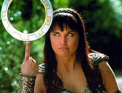 Xena balances her chakram on her upheld index finger