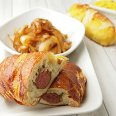 Pretzel Wrapped Brats with Cider Braised Onions