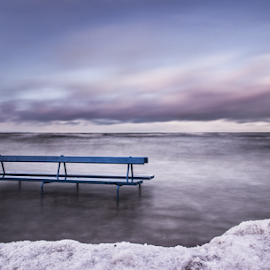 A bench by Julija Moroza Broberg - Landscapes Weather ( bench, freedom, waterscape, beach, storm, freezing, frozen, blue sky, high water, level, cold, ice, snow, timing, alone, water, wind, edge, windy, water level, sea, seascape, winter, special, view )