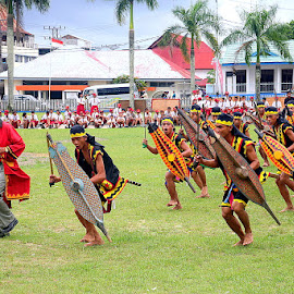 Warriors performing a traditional dance by Leong Jeam Wong - People Musicians & Entertainers ( warrior, spear, tradition, ceremony, shield, dance, leap, nias, wall, sword, jump )