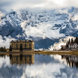 Misurina lake in the dolomiti by Митч Зул - Landscapes Mountains & Hills ( wood, leaf, house, travel, sky, cold, nature, tree, autumn, foliage, shadow, buildings, weather, pine, light, grass, trekking, forest, lake, shape, country, lavaredo, magic, environment, winter, season, plant, reflection, ray, beauty, road, landscape, hotels, mountains, dolomiti, path, rain, alps, water, peaceful, park, green, beautiful, morning, color, sunset, outdoor, cloud, mist )