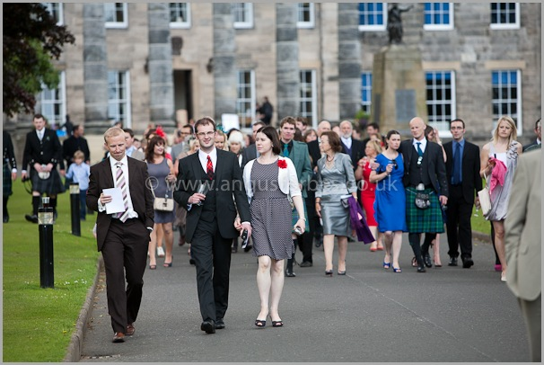wedding guests follow pipe band to dinner