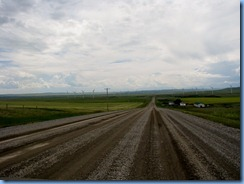 1183 Alberta - gravel roads between Head-Smashed-In Buffalo Jump Interpretive Centre and Pincher Creek - canola field   wind turbines   mountains ahead