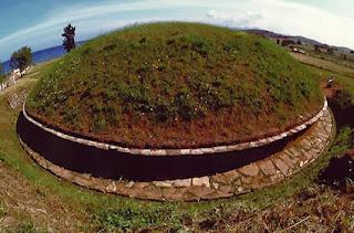 заросший зеленой травой псевдокупол тумулуса, подземной гробницы этрусков на фоне синего неба
