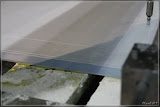die Ränder der noch feuchten Papierbahn werden mit einem Wasserstrahl abgeschnitten