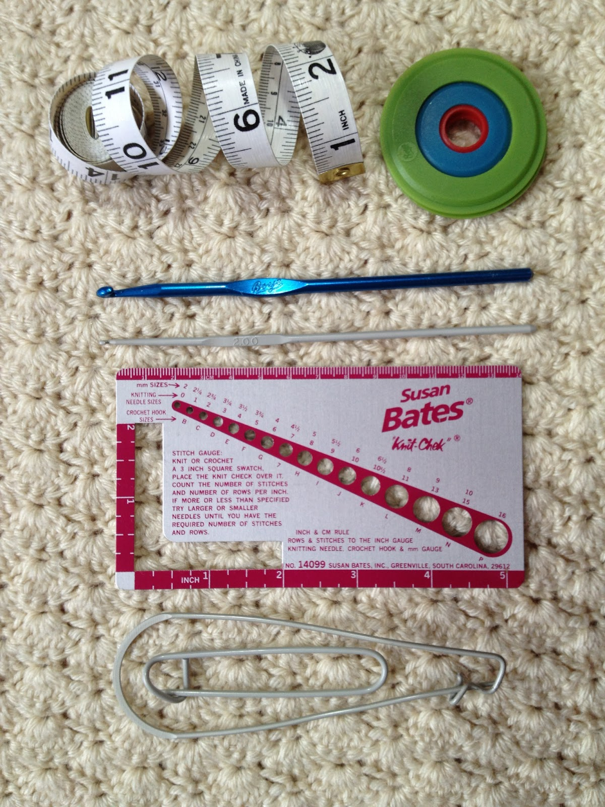 MEASURING TAPE, POM POM MAKER, CROCHET HOOKS, NEEDLE GAUGE, STITCH HOLDERS
