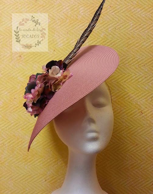 tocado color nude con adorno de hortensias en varios colores y pluma de faisán en natural para boda de día