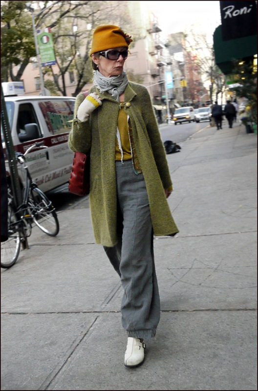 w olive green collr button coat grey slacks vest grey scarf burnt orange hat fingerless knit gloves sunglasses ol