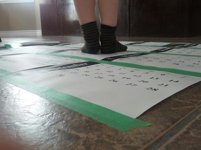 Close up of preschool child standing on a calendar hop game