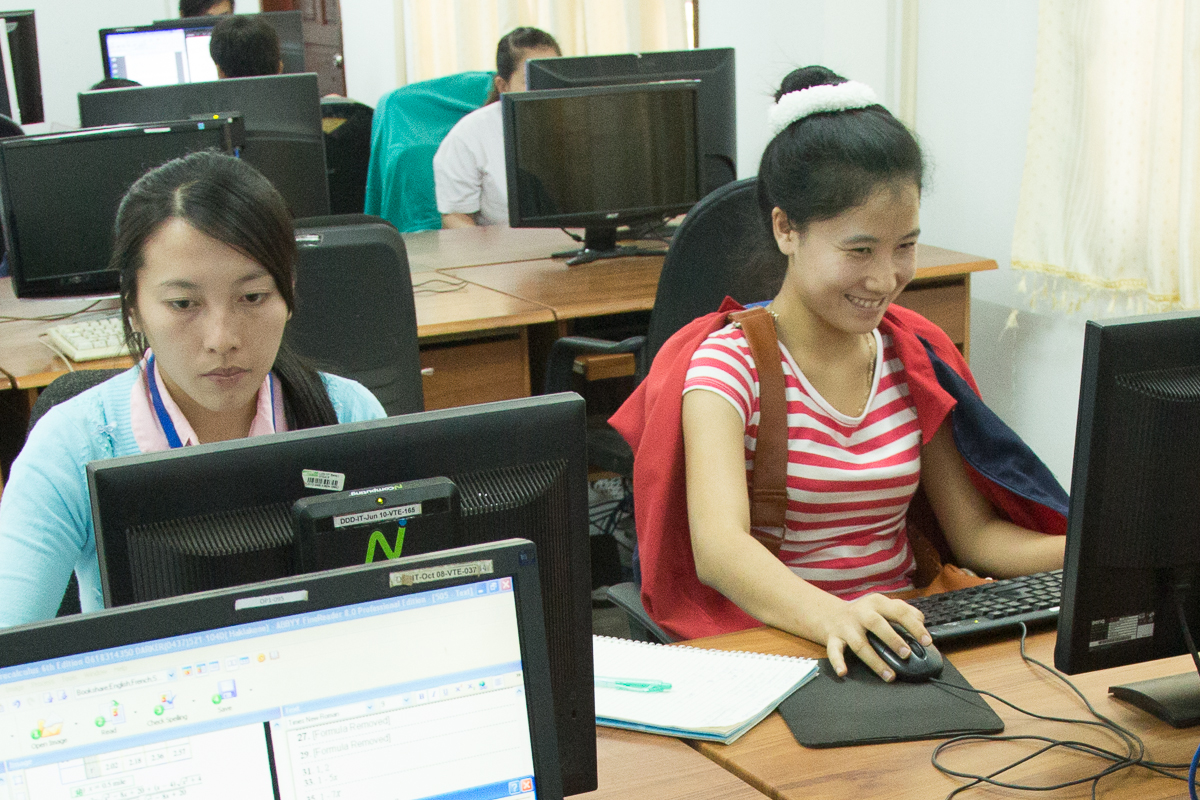 Two students work at PCs