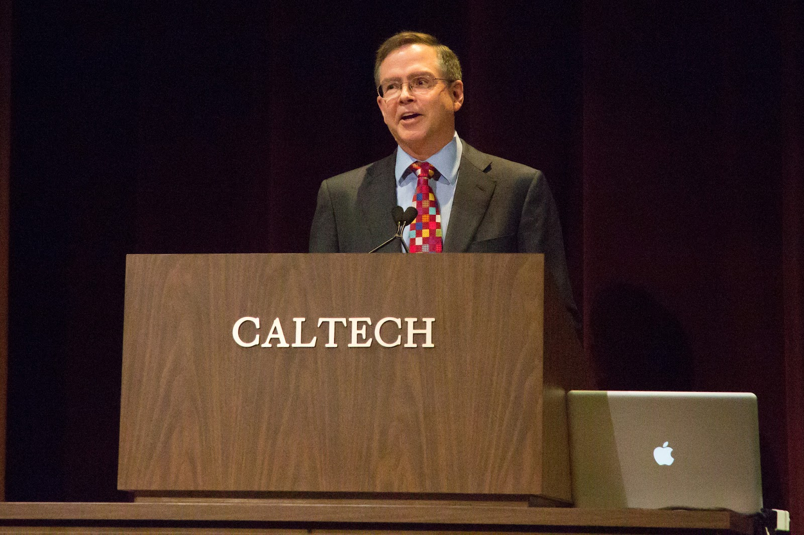 Jim in a suit behind a podium with the word Ccaltech""