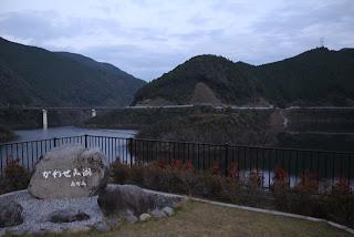 右岸駐車場より石碑とダム湖を望む
