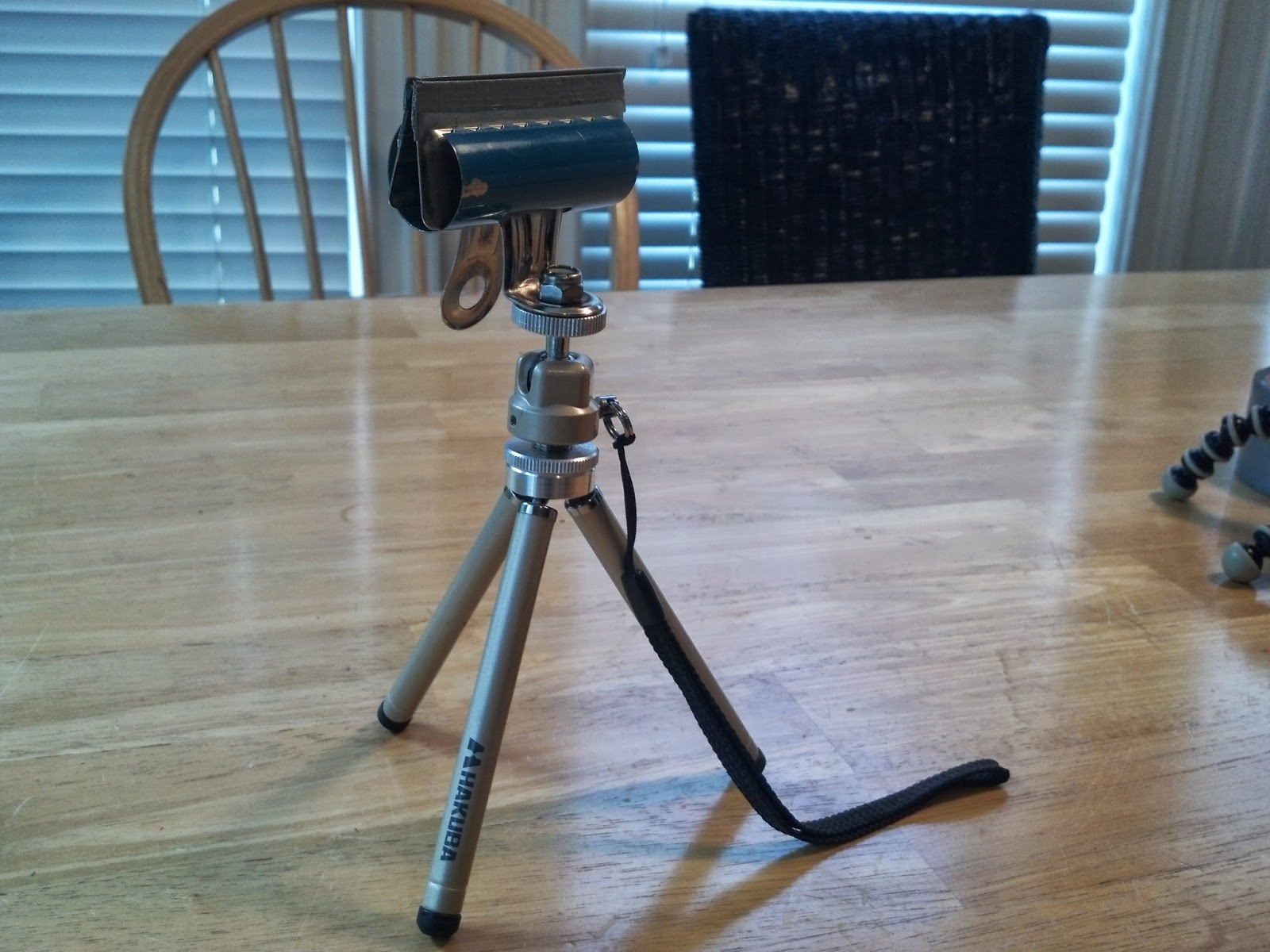 Bulldog clip attached to tripod to hold smartphone
